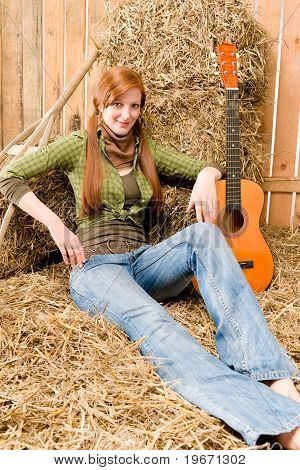 Young Country Woman Sitting Hay With Guitar