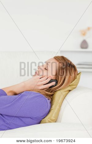 Profile Portrait Of A Serene Red-haired Woman On Phone While Lying On A Sofa