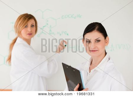 Cute Scientist Writting A Formula Helped By Her Assistant