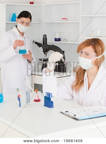 Dark-haired And Blond-haired Scientists Conducting An Experiment