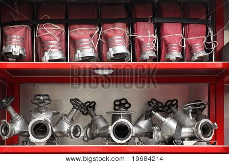 Fire cocks and hoses accurate organized inside big red fire engine