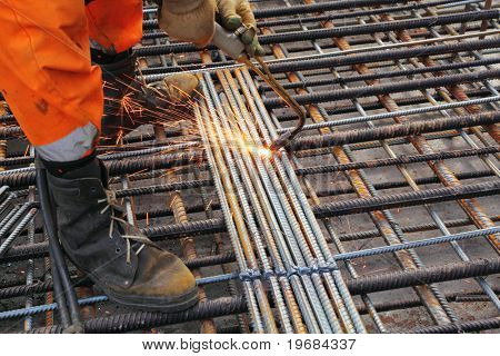 Worker legs in orange clothes weld metal grating by acetylene torch