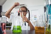 Elementary student doing scientific experiment with green chemical at science laboratory poster
