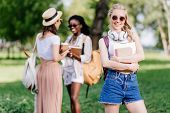Beautiful Smiling Blonde Student With Headphones Holding Books While Friends Talking Behind In Park poster