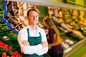 foto of grocery store  - Shop assistant in a supermarket at the vegetable shelf - JPG