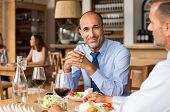 Smiling mature businessman sitting at cafe with partner enjoying meal. Portrait of senior businessma poster