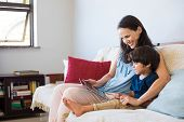 Mother and son sitting on sofa using digital tablet. Happy mom and little boy using tablet with touc poster
