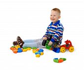Little Boy Sitting Among Toys On Floor