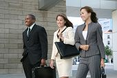 stock photo of team building  - An attractive business team walking composed of two women and a man - JPG