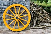 stock photo of stagecoach  - An old antique yellow wooden wagon wheel leaning against a stone wall - JPG