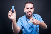 Portrait Of Male Pediatrician Showing Number Nine And Peace Gesture poster