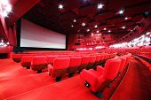 stock photo of movie theater  - View from stairs on screen and rows of comfortable red chairs in illuminate red room cinema - JPG
