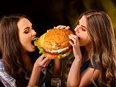Women eating fast food. Gils eat hamburger with ham . Two friends female bite the burder junk from t poster