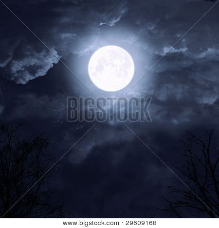 moon on a dark sky with clouds in the trees