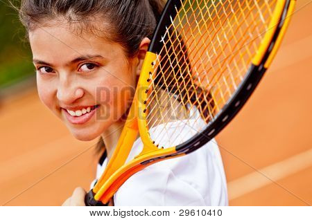 Female tennis player holding a racket and smiling