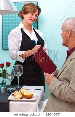 Photo of a waitress in a restaurant taking a food order from a mature male who is sat at a table holding a menu.