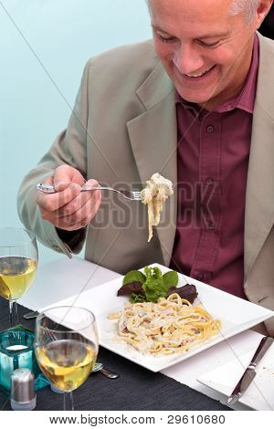 Photo of a man eating pasta in an Italian restaurant.