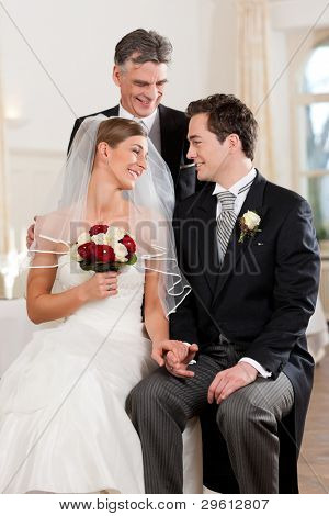 Bridal couple waiting for ceremony - the brideâ??s father is giving last tips