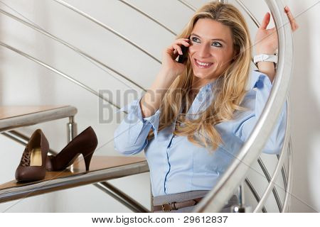 Businesswoman making a phone call and sitting on the stairs in her apartment