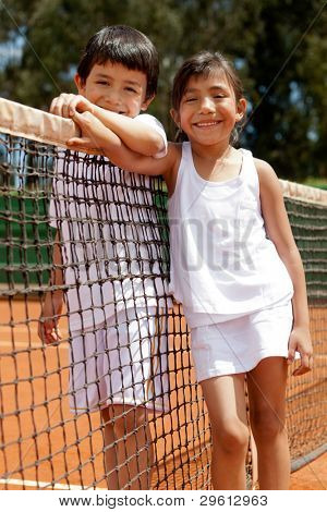 Loving sibblings at a tennis court next to the net