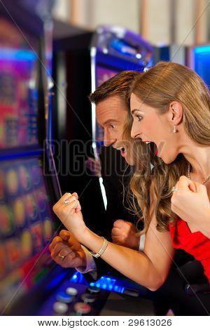 Couple in Casino on a slot machine winning and having fun