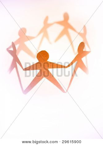 Paper doll people in a circle holding hands on plain background