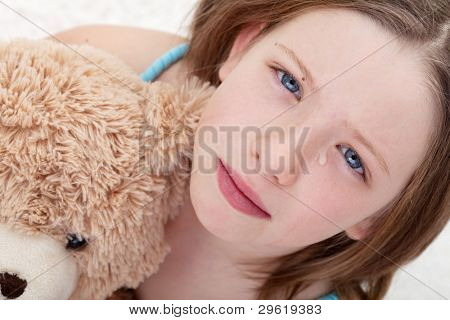 Beautiful sad girl holding teddy bear and crying - closeup