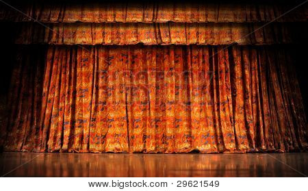 Orange stage curtains with reflection on wood floor