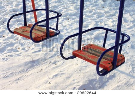 Children's swings against the winter snow