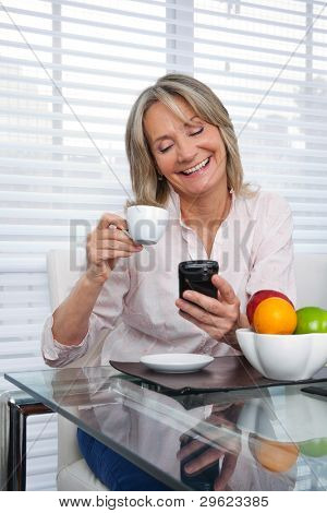 Smiling mature woman using cell phone while having tea