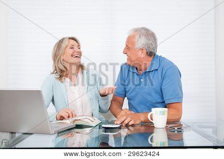 Happy couple at dining table working on laptop on house finance