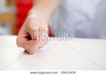 Mão de farmacêutico segurando o comprimido do medicamento na farmácia drogaria.