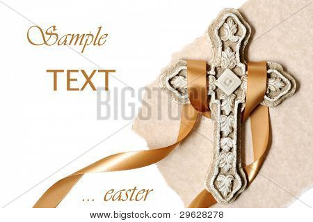 Easter background image of small ornate stone cross with gold satin ribbon and parchment paper on white background with copy space.