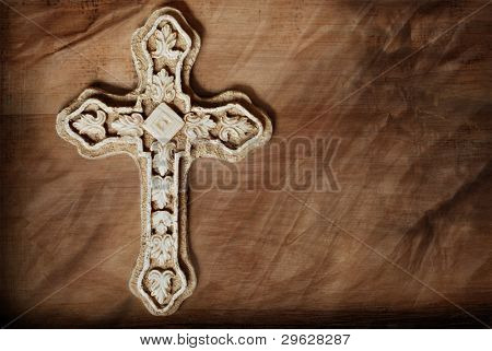 Artistic macro image of ornate stone cross on wood background with layers of texture added for effect.  Copy space included in design.