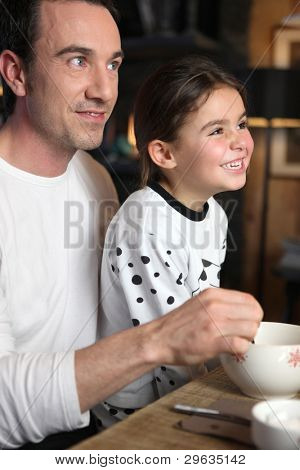 Father and daughter laughing at breakfast