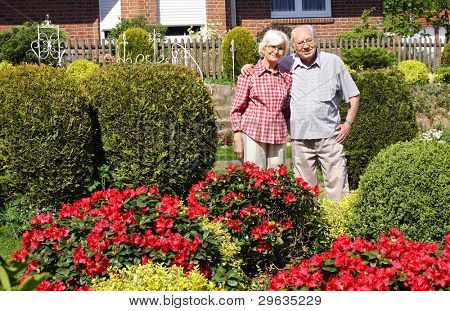 Senior couple in their garden with bushes and flowers