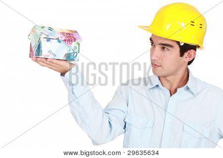 Architect examining house made from money