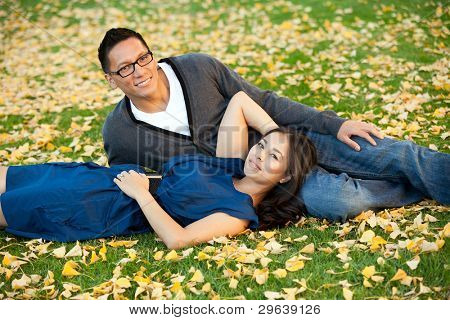 Ethnic young couple sitting in a pile of leaves