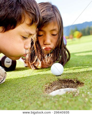 Golf players cheating blowing to get the ball into the hole
