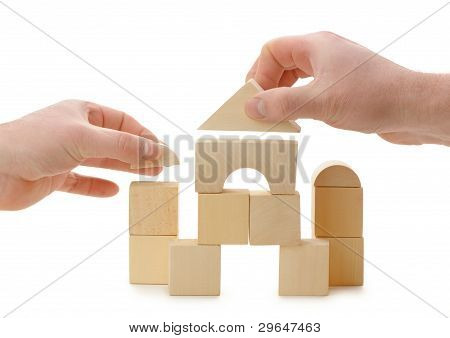 The Hands Establishes A Toy Roof On Wooden Cubes