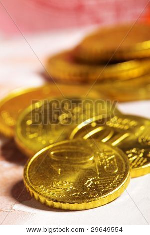 Heap of ten euro cent coins close up on banknote