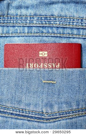 Red biometric passport in jeans pocket close-up