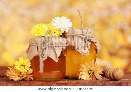 two jars of honey and wooden drizzler on table on yellow background