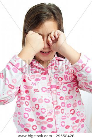 Sleepy young girl wearing pajamas isolated on a white background