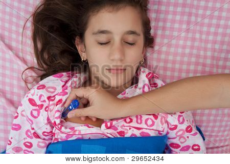 Portrait of a beautiful hispanic girl sick with fever while a hand with a thermometer measures her temperature