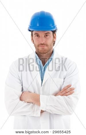 Confident young engineer standing arms crossed, wearing hardhat.?