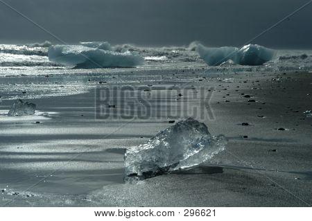 Ice Block From Glacier On Black Lava Beach
