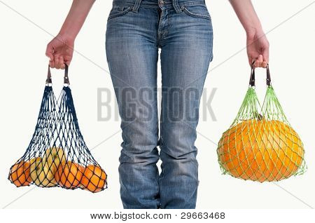 Woman carrying shopping bags with yellow fresh fruits isolated on white background