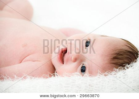 Close up portrait newborn baby lying in bed