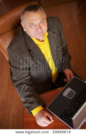 Portrait of a happy successful mature business man working with laptop in a wood paneled office.